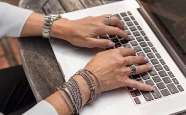 Woman wearing a lot of bracelets and rings taking a survey on her computer