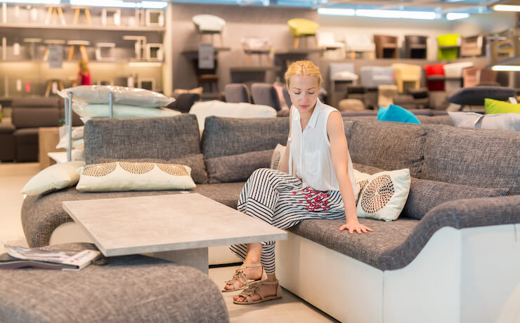 Woman testing out couch at furniture store