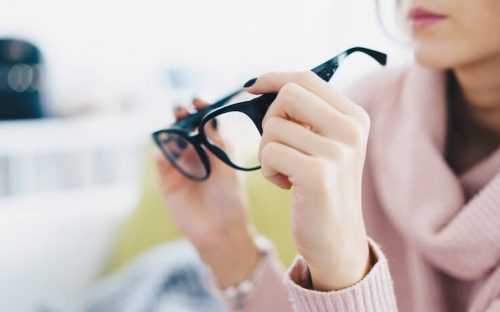 Woman looking at glasses at discount store