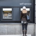 Woman using a self-service ATM machine at a bank