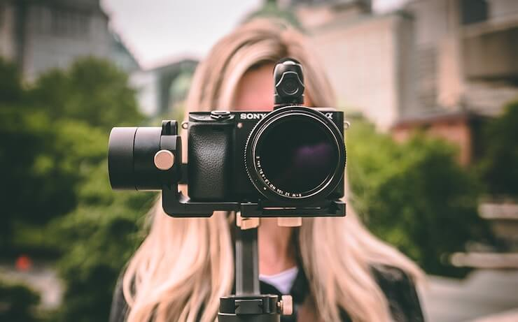 Woman with camera on a gimbal recording a youtube video