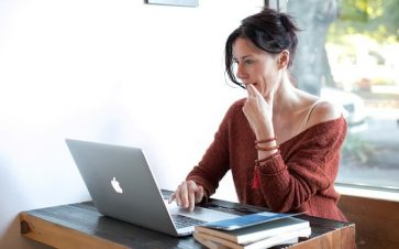 Woman on her computer at a cafe looking for coupons online