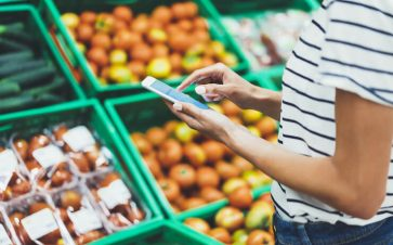 Woman using her cell phone to compare prices while grocery shopping at a store
