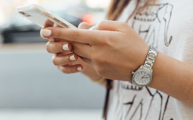 A woman with white manicure and wearing a silver watch using her iphone