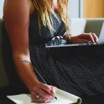 Woman wearing a dress working on her laptop while taking notes in her notebook