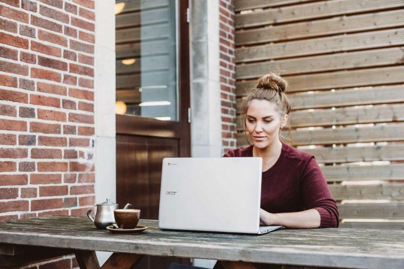 women typing on old laptop